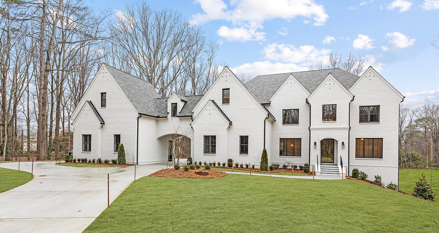 Painted white brick house with black framed windows and doors. Transitional home design.