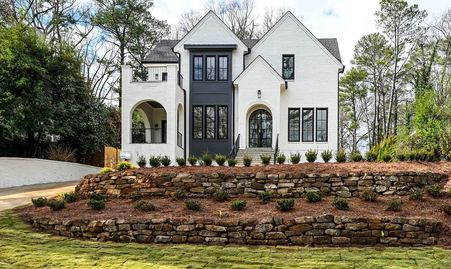 painted white brick house with black paneling and black railings with a black arched top front door