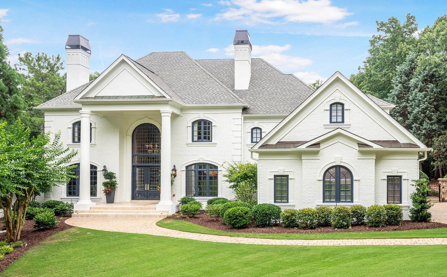 Traditional styled white brick house with stucco accents and trim. Gray shingled roof with brown metal accents. Huge front columns. Blue window and doors frames with a blue front door.