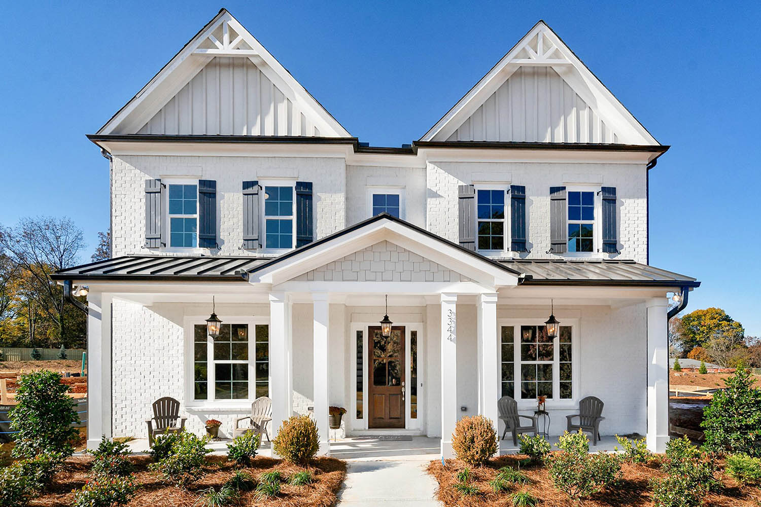 White and black transitional home design. Painted white brick with black shutters and vertical siding accents. Real wood front door.