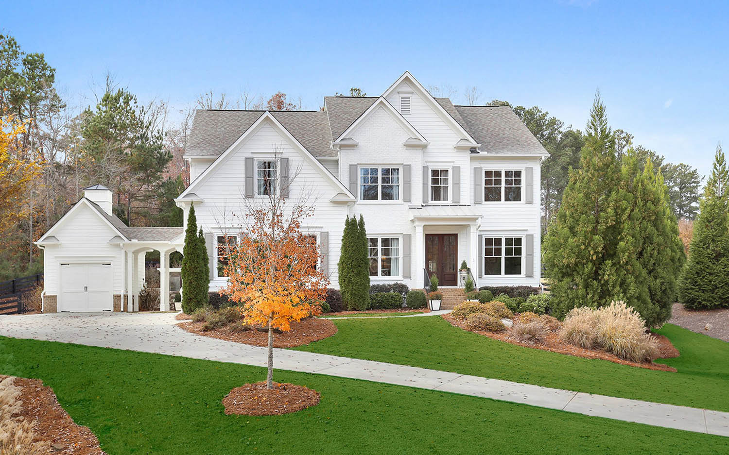 white brick house with white vinyl siding, gray shutters, red brick veneer and porch, stained wood front door.