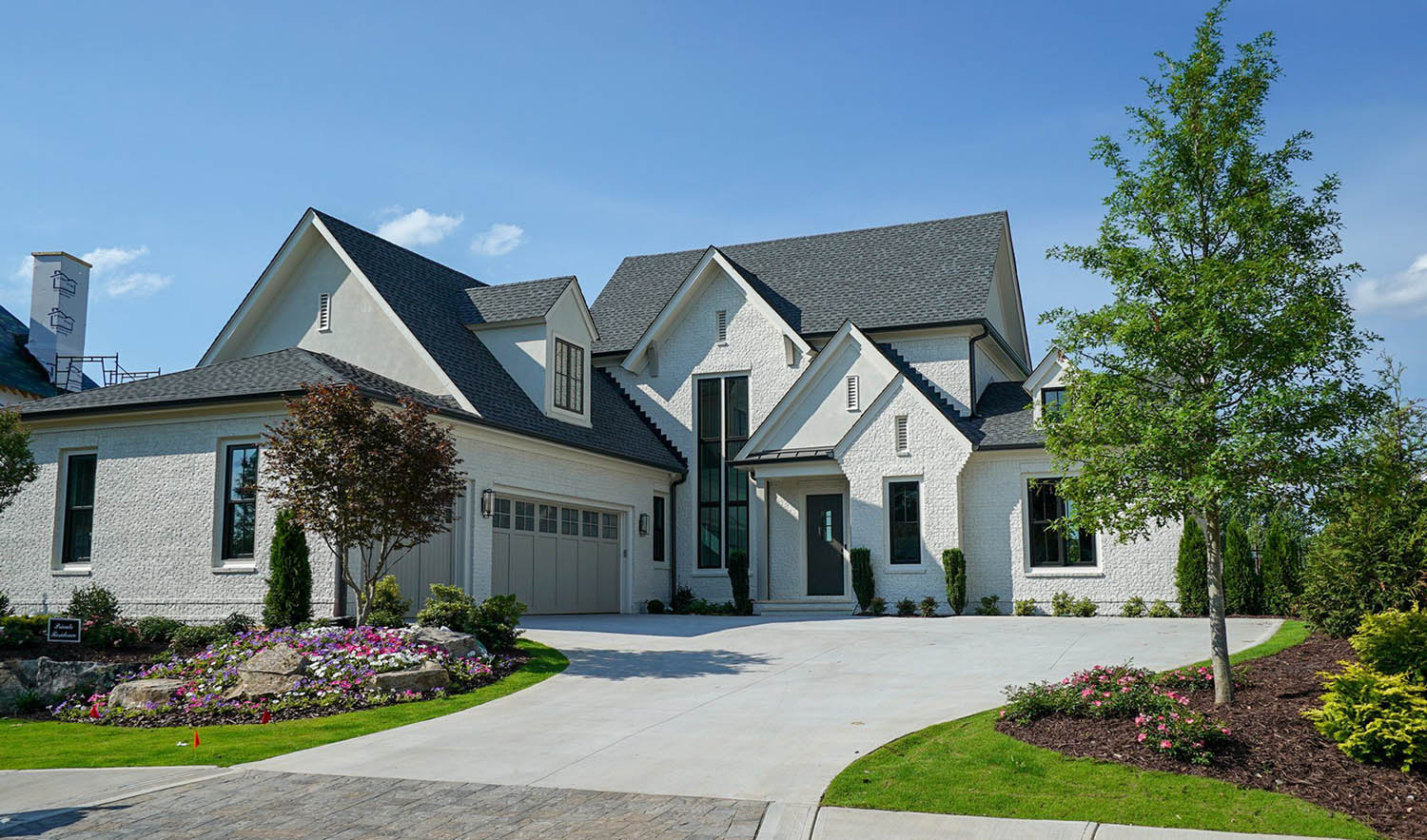 White brick house with stucco. White and black exterior design with gray garage doors. Black shingled roof with black metal accents. Black gutters.