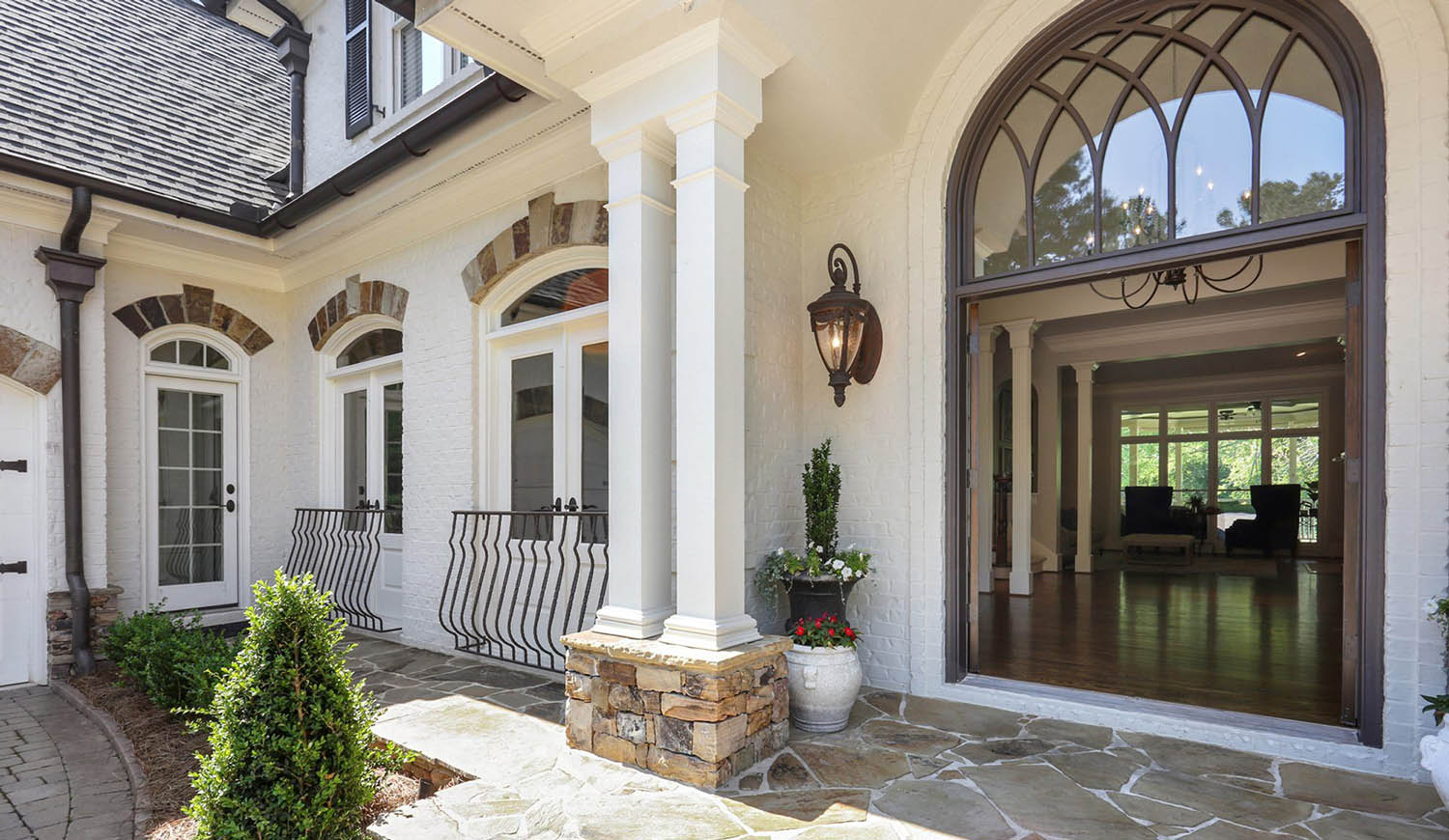 front porch white brick house with stone accents and veneer white columns dark brown front door