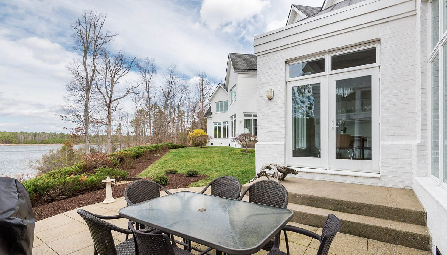 painted white brick house back porch with concrete patio and black chairs