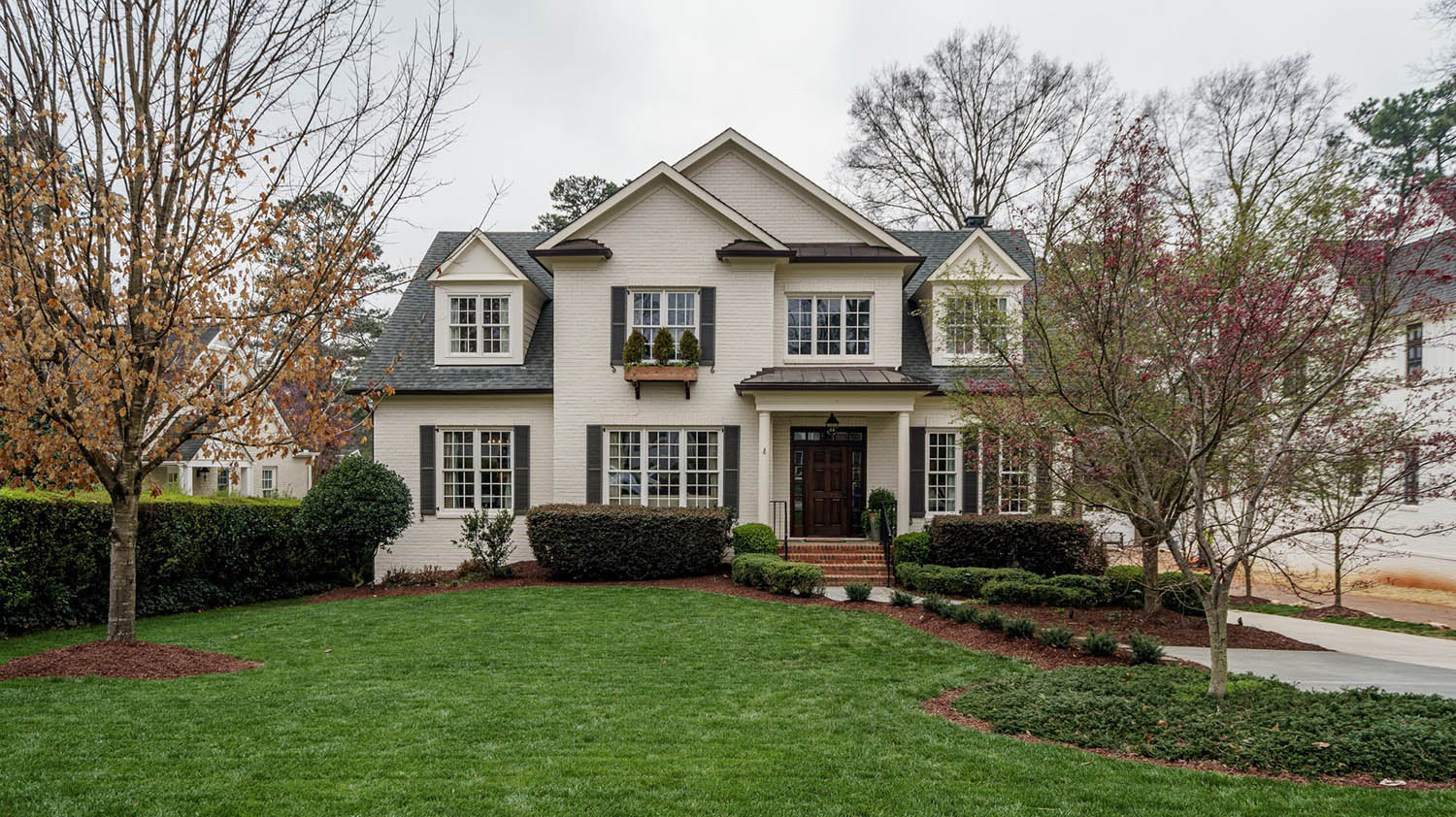 painted white brick house with red brick front steps, black shutters, roofing and railings