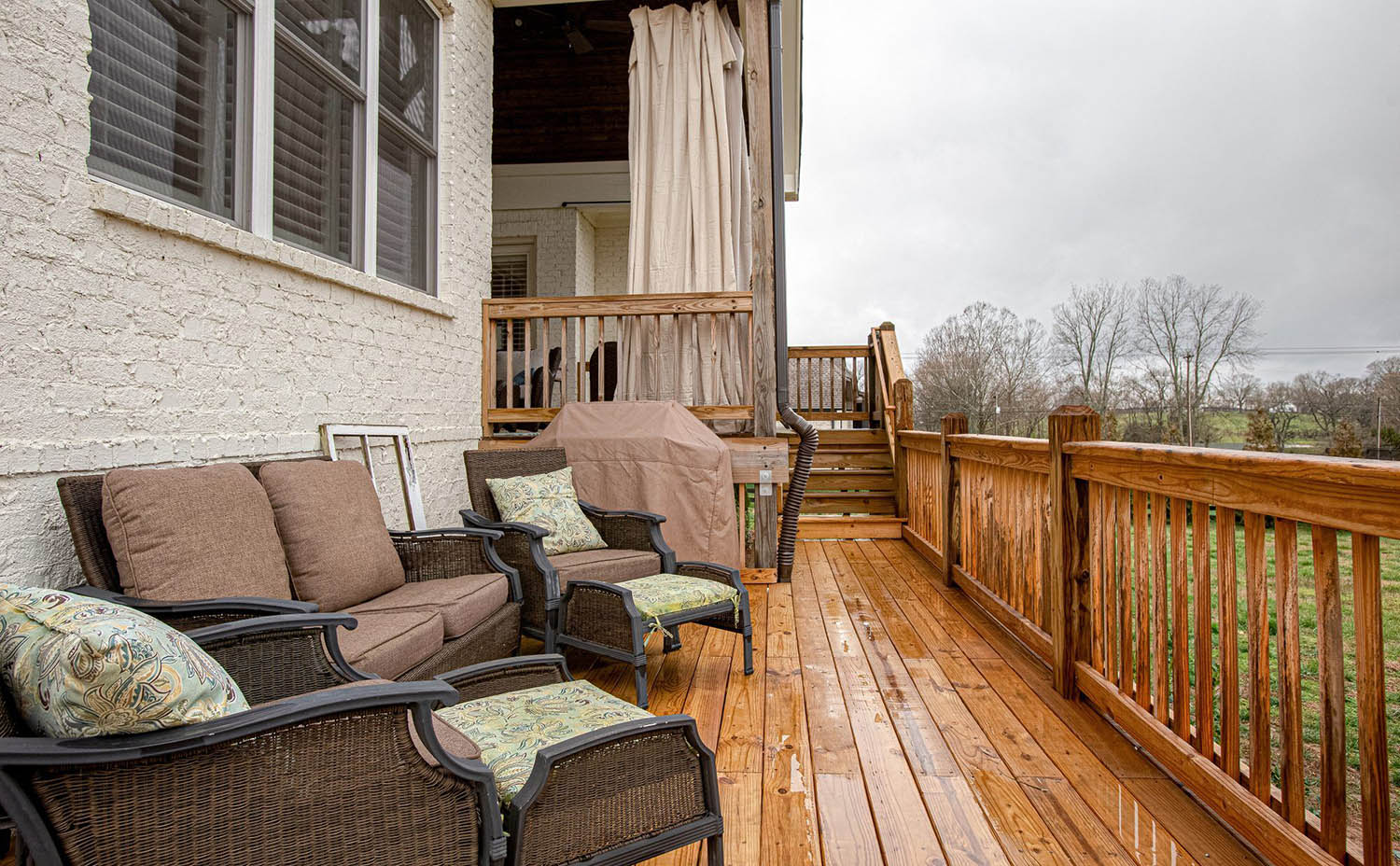 painted white brick house with real wood deck and outdoor furniture