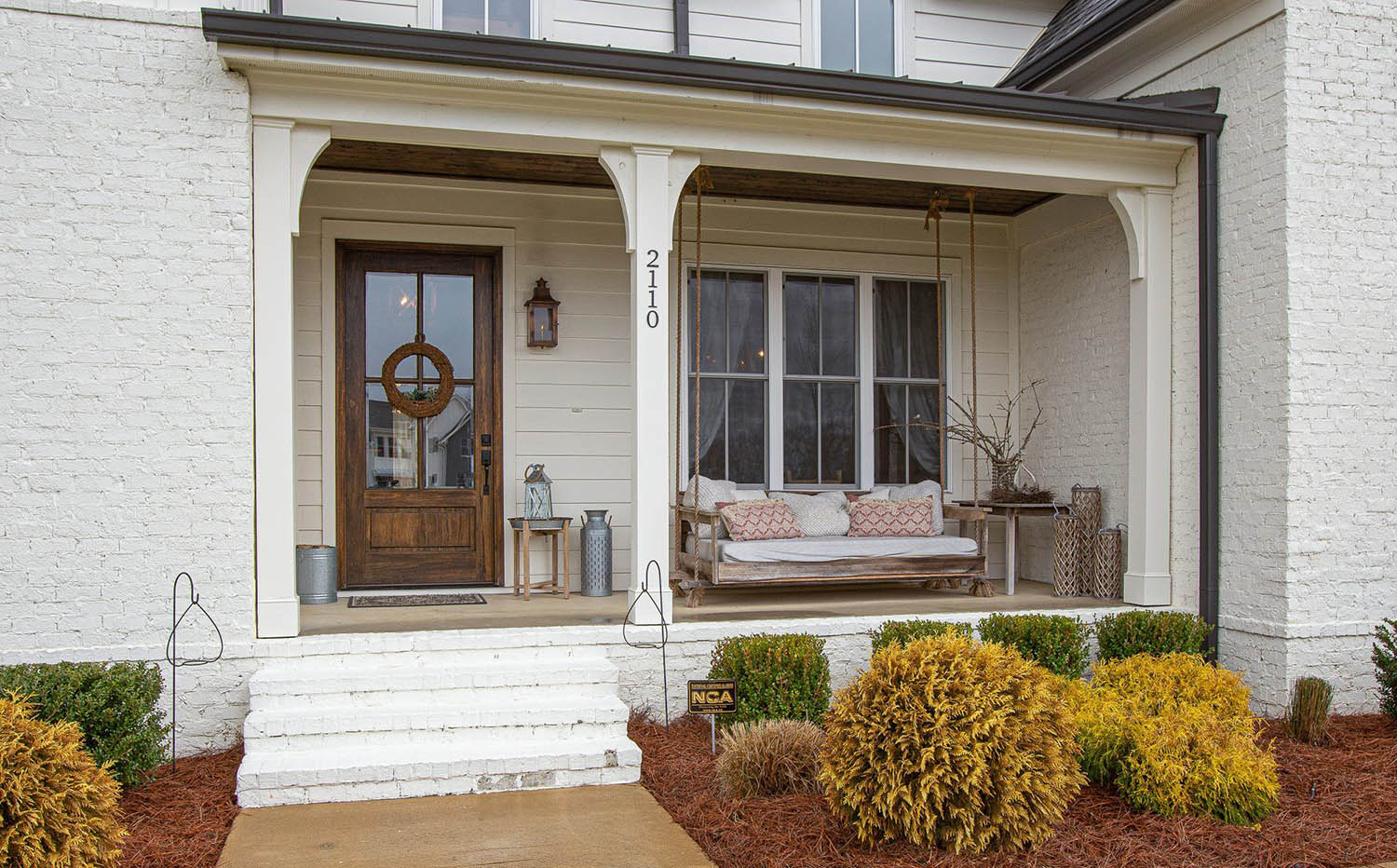 Painted white brick home with country style front porch and swing seat. Real wood soffit and stained wood front door.