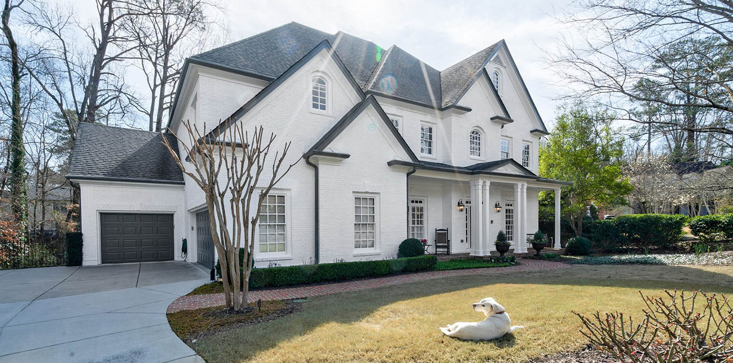 transitional white painted brick home with black roof and gutters. Black garage door. White columns.