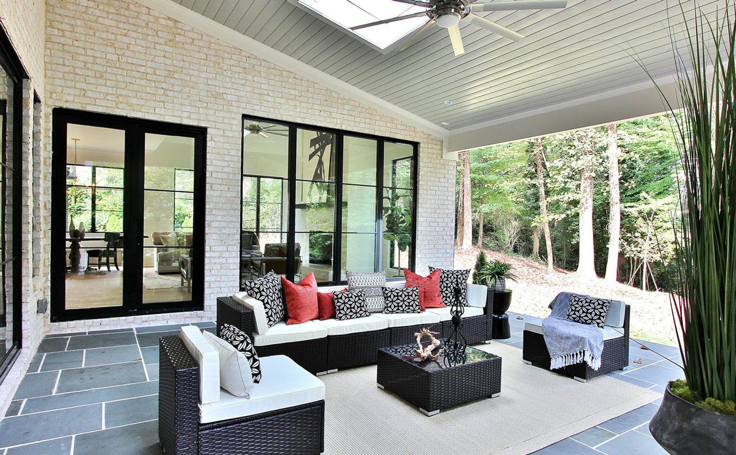 white brick wall with black framed windows and doors blue stone patio back porch