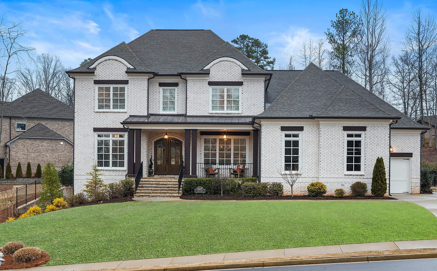 white brick home with black roof and darm brown stained front door