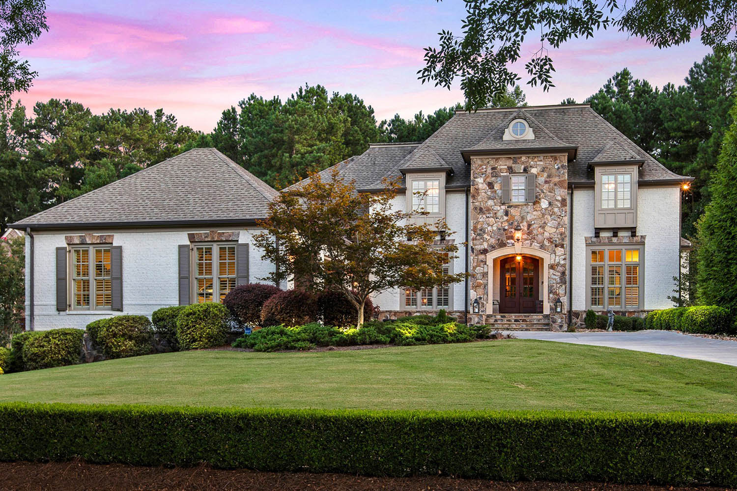 White brick home with real stone veneer and gray shutters. Dark shingled roof with black gutters. Stained real wood front door.