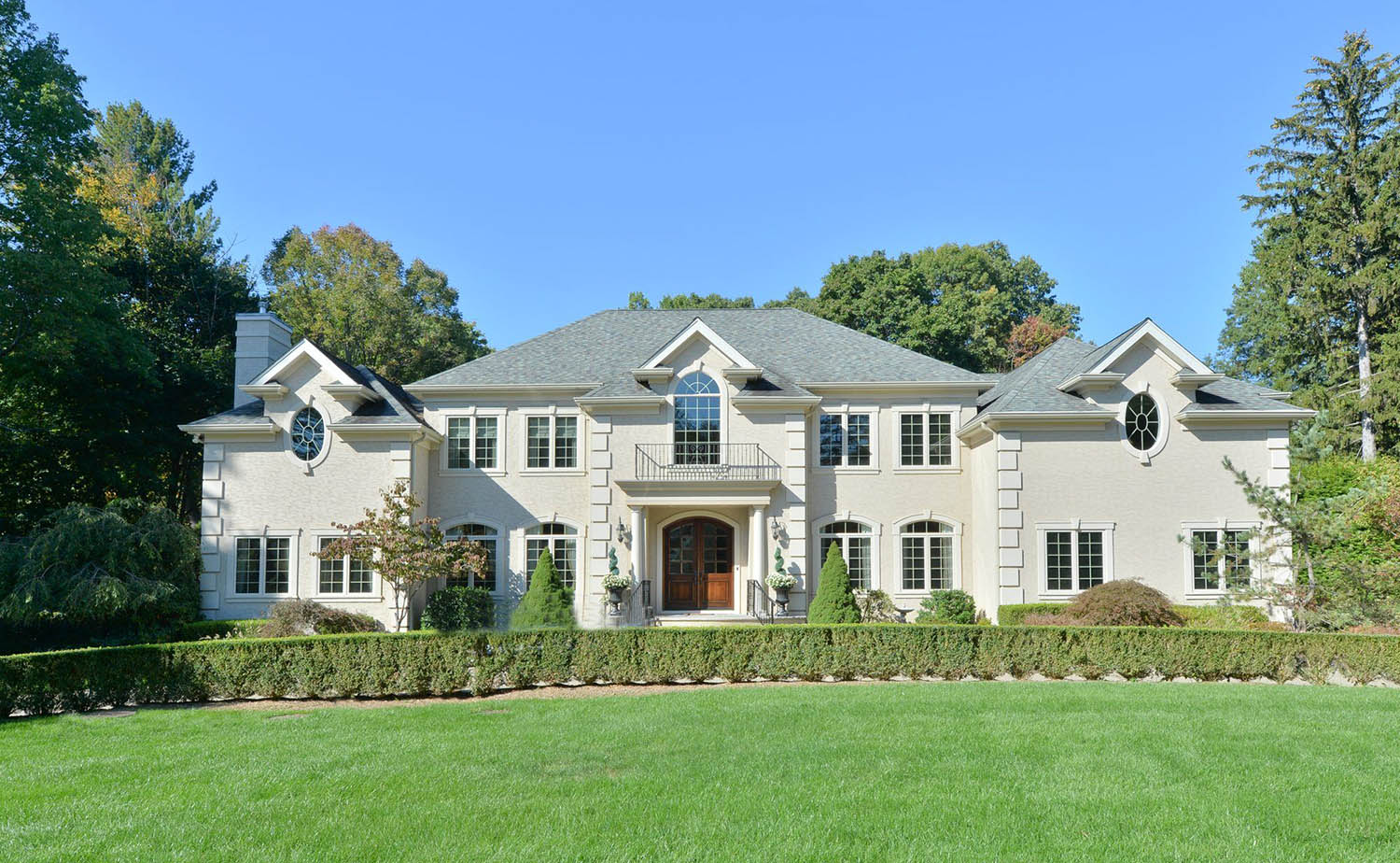 estate home with white brick siding and stained brown real wood front door