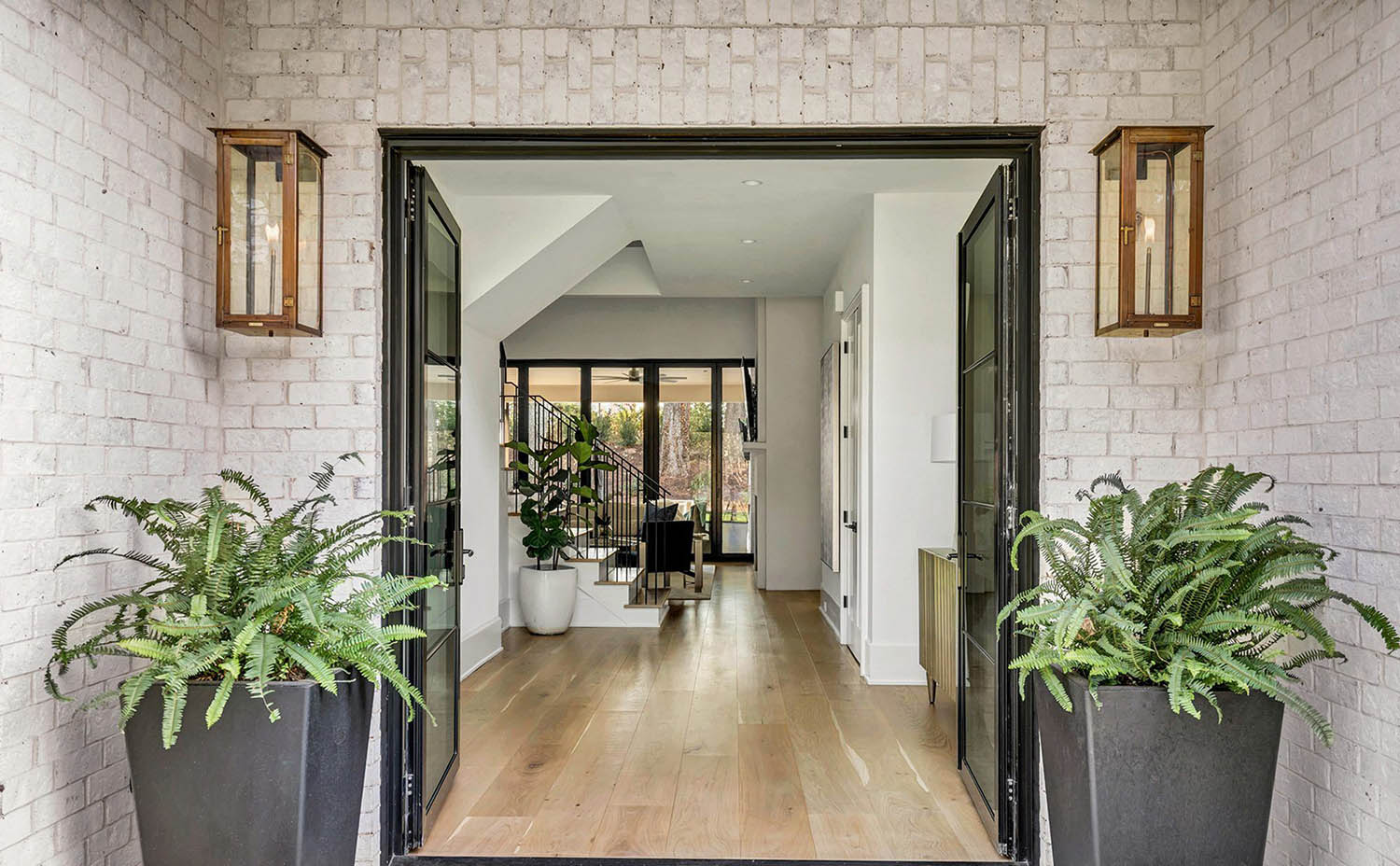 white brick walls entryway with potted porch plants and brass pendant lighting