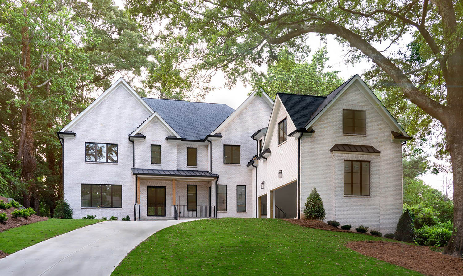 transitional home with white brick siding and black framed windows and doors