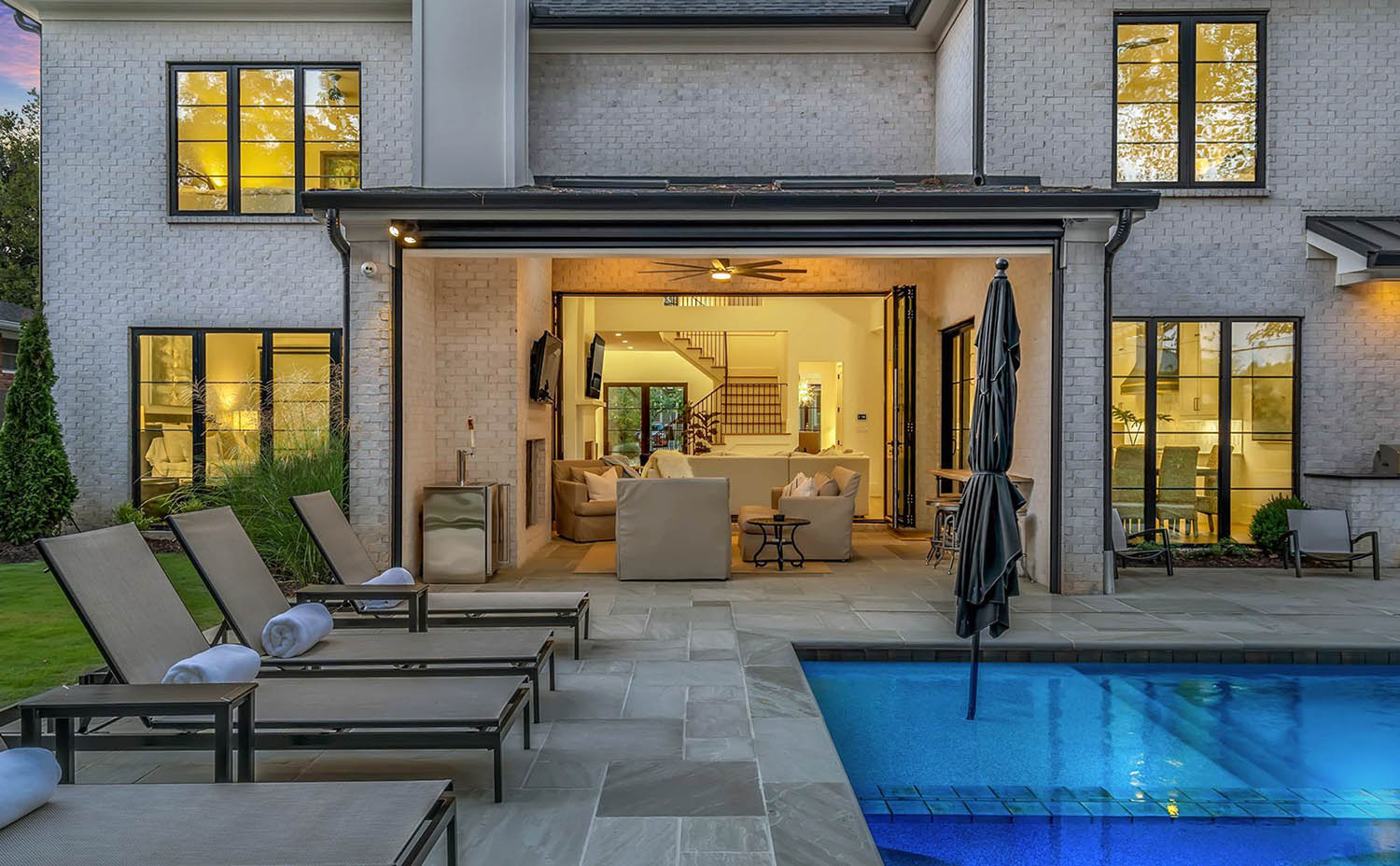 rear porch and pool white brick with black frames and blue stone patio