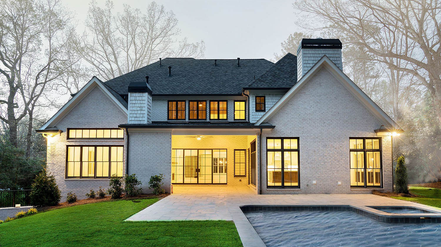 custom new home with white brick walls and black framed windows and doors