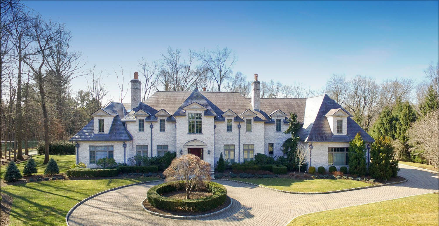 Large estate home with real white brick veneer siding.