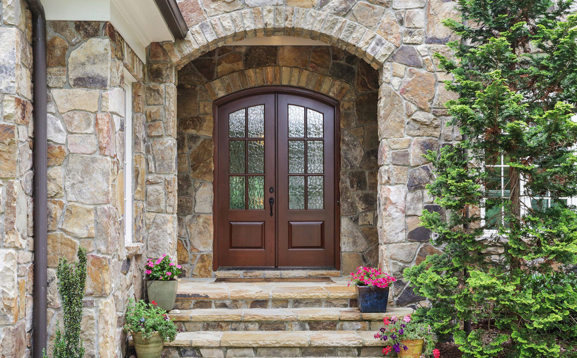 Brown arched front door with earth toned stone veneer. Matching stone steps with potted porch plants.