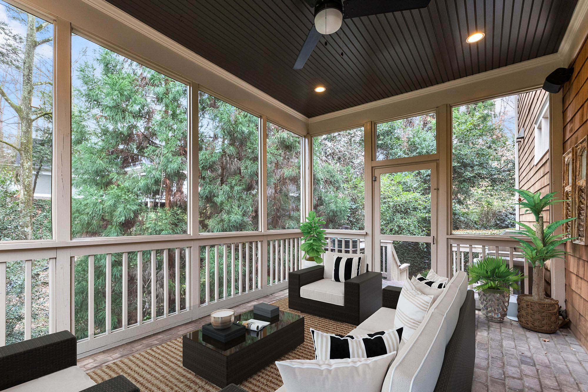 covered screened porch patio with red brick floor, black wicker furniture with white cushions.