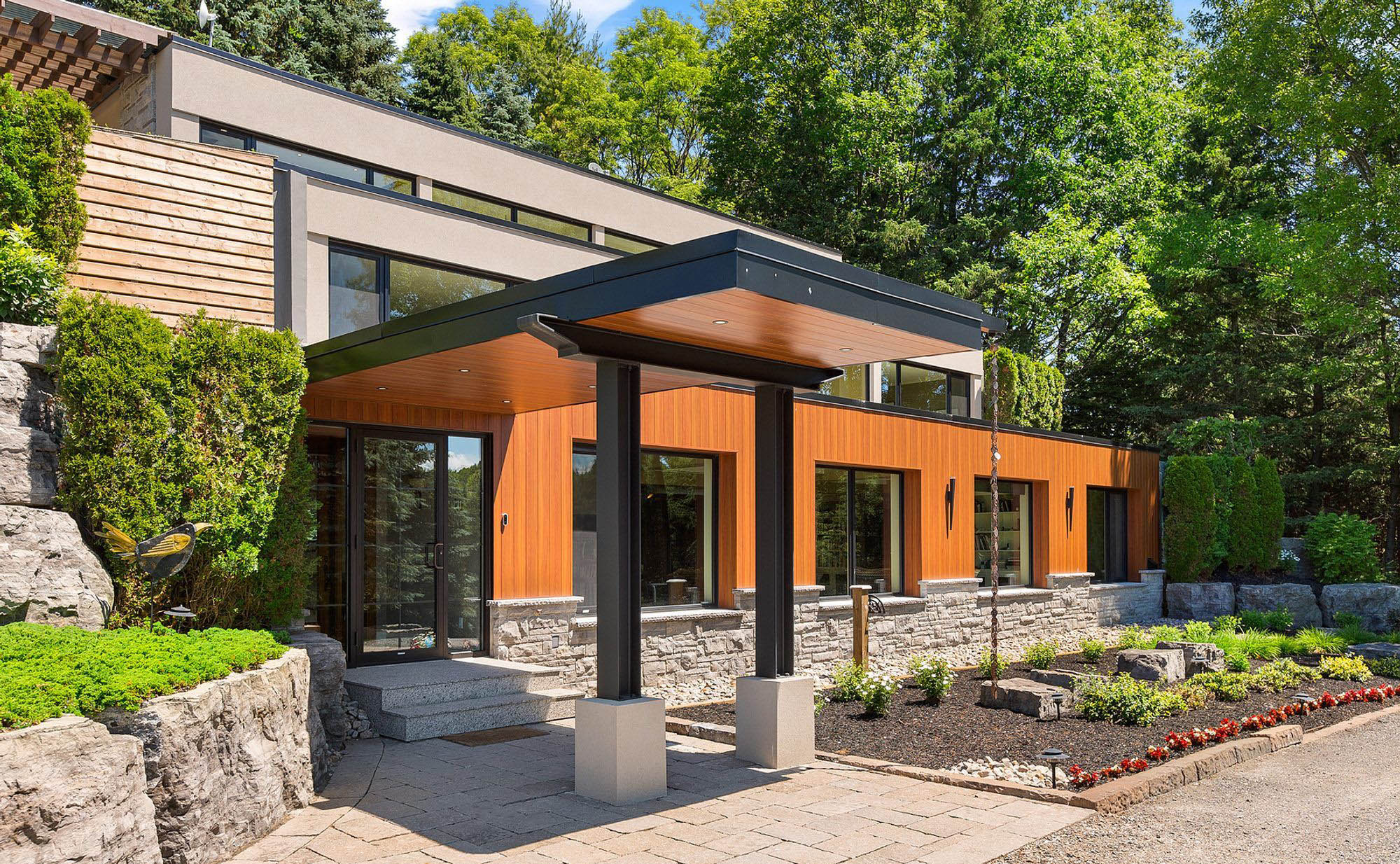 Modern home with black metal fascia and wood soffit including recessed lighting.