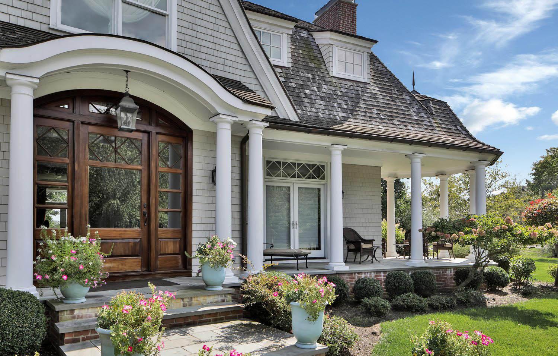 Beautiful custom home with white Azek soffit & fascia. Dark brown gutters. Wood front door, red brick & cedar shake siding.