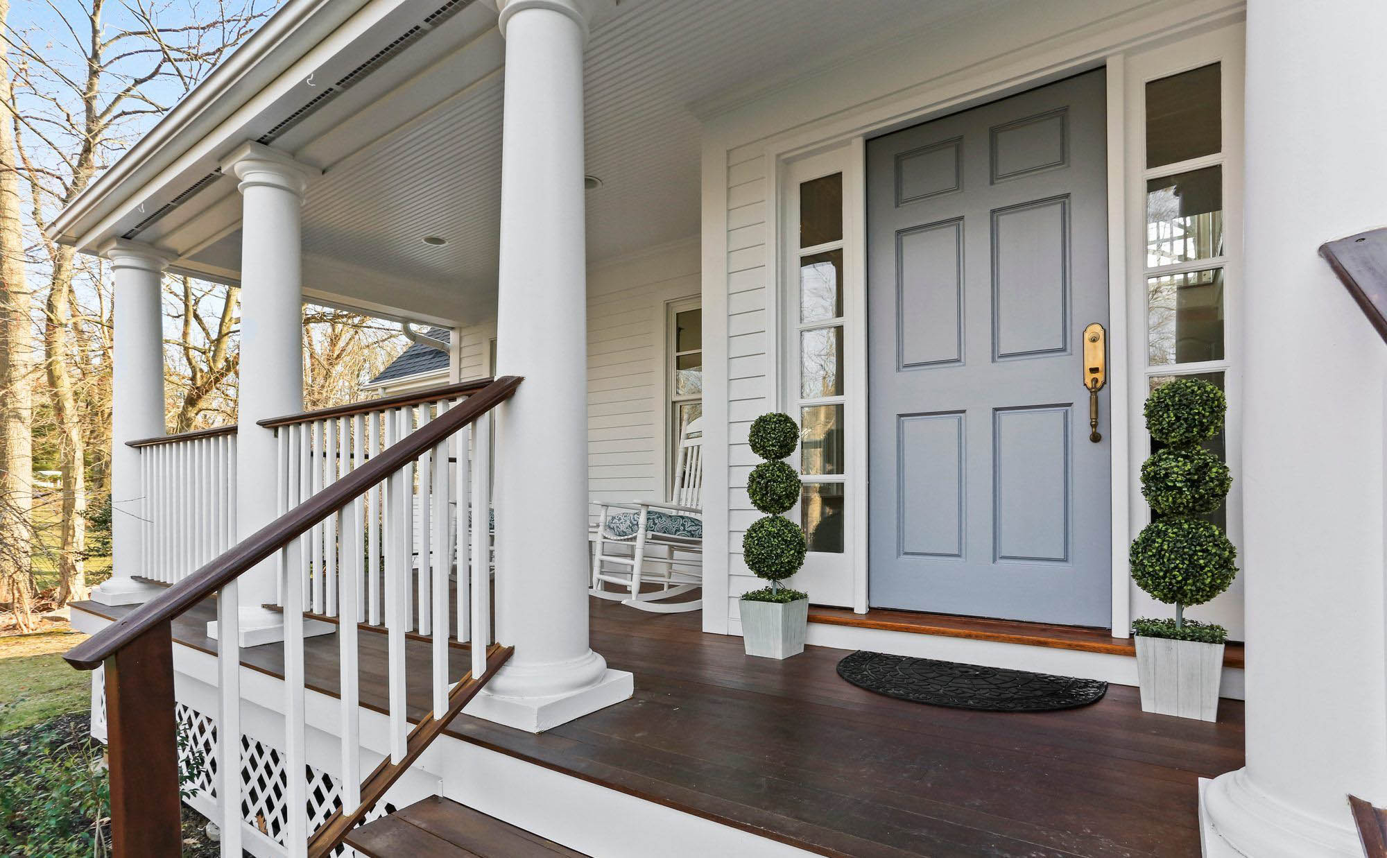 White composite fascia and bead board porch soffit. White columns, balusters, trim and siding with wood hand rail.