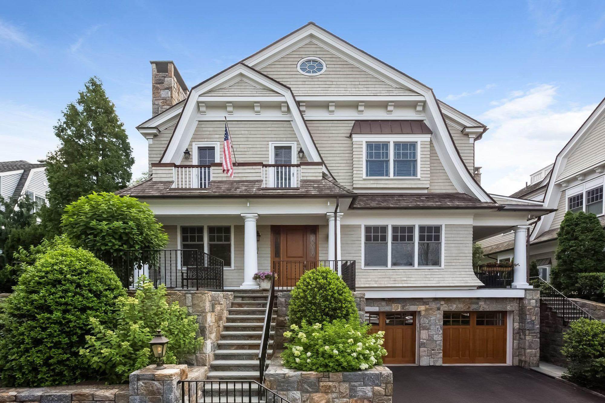 Beautiful custom shingle style home with Azek soffit and fascia. Cream cedar shake siding with real stone veneer.