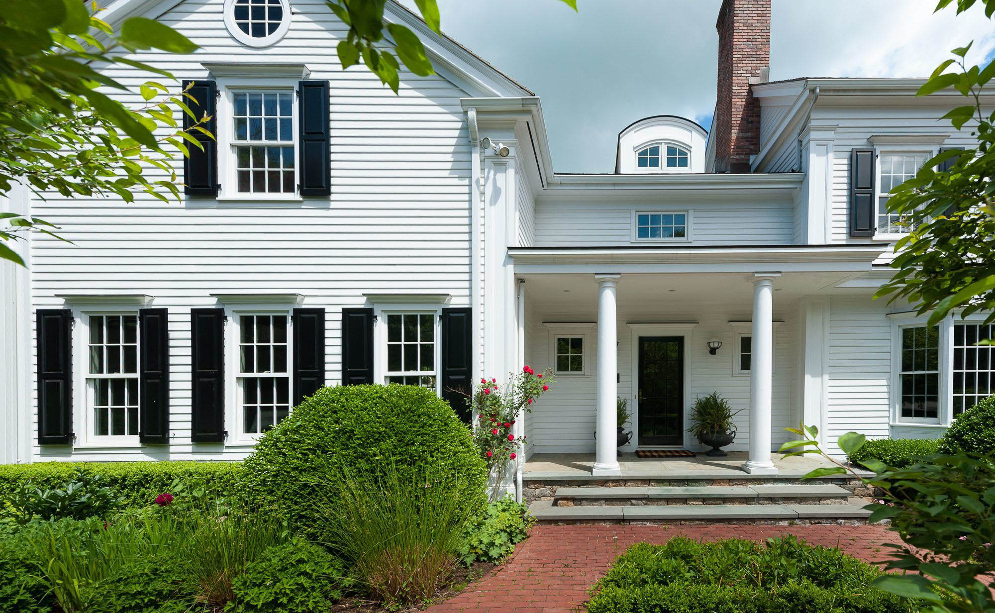 Modern Colonial home with white Azek soffit and fascia. White siding with black shutters.