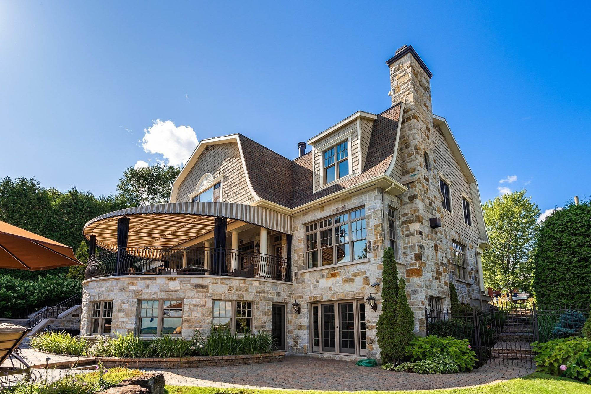 Cream colored vinyl soffits and fascia on this beautiful custom home featuring real stone and cedar shake siding.