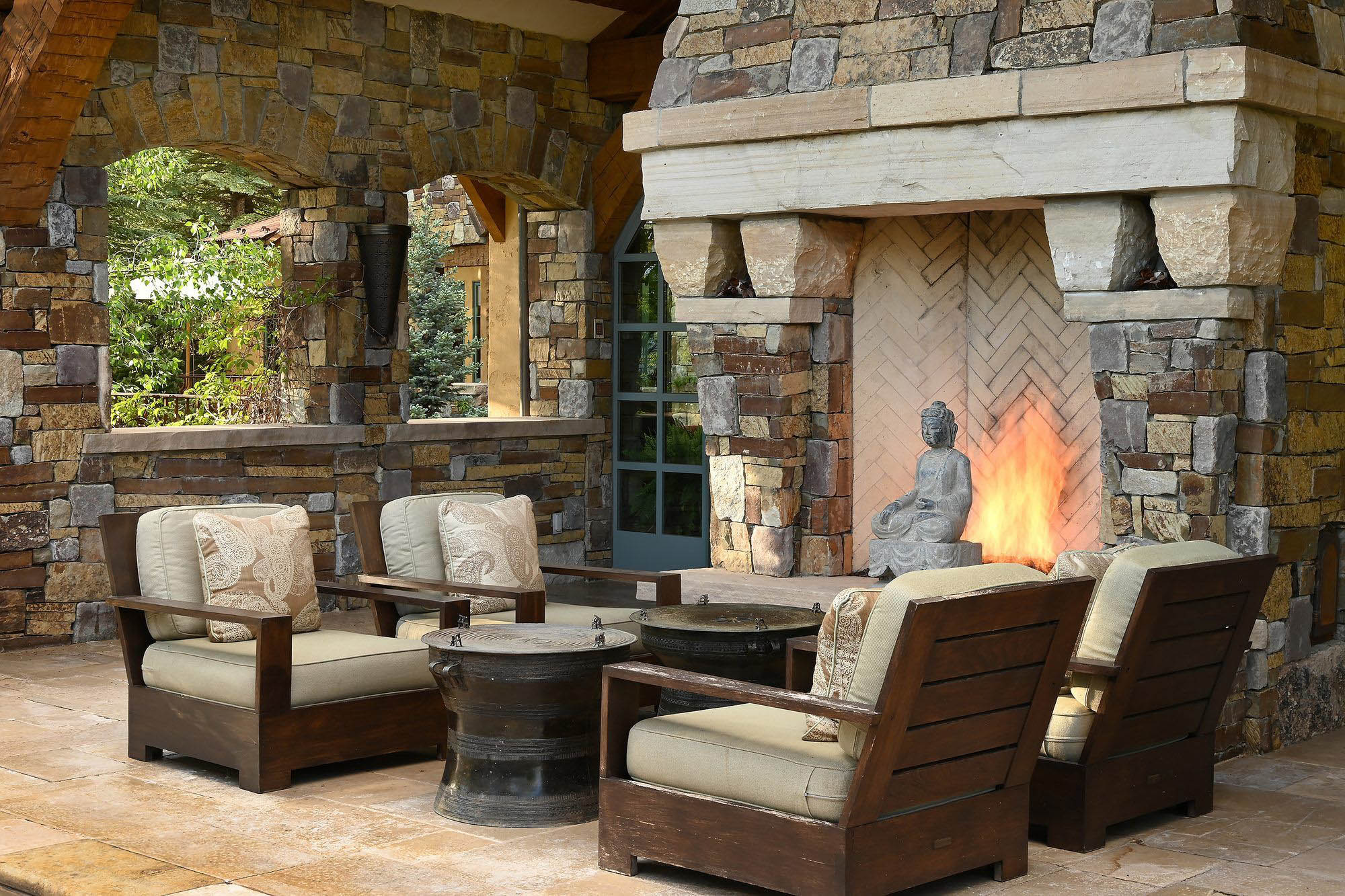 This beautiful outdoor living space features a huge real stone fireplace with matching stone walls, stone tile flooring and wood furniture.