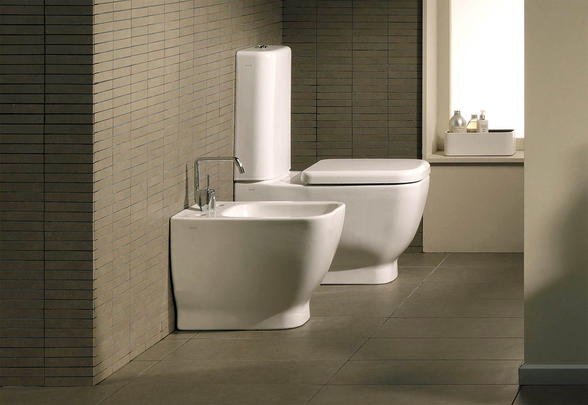 side by side matching modern bidet and toilet in a modern master bathroom.