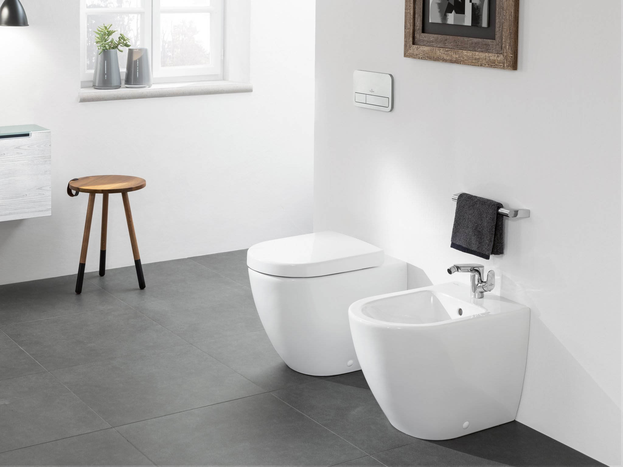 matching white cermaic floor mounted side by side toilet and bidet with electronic controls