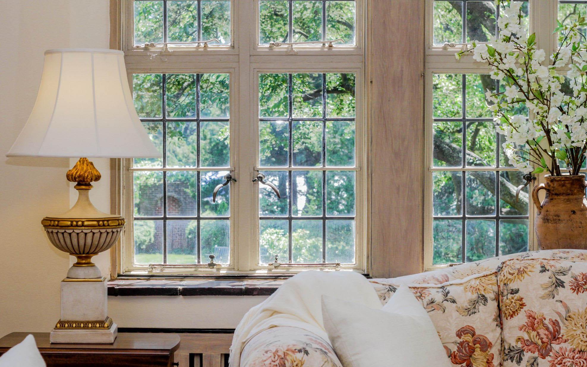 monochromatic living room closeup sofa lamp end table and window trim