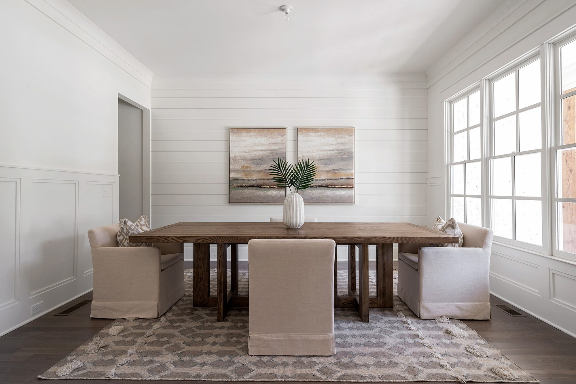 hand knotted dining room area rug in a transitional room with shiplap