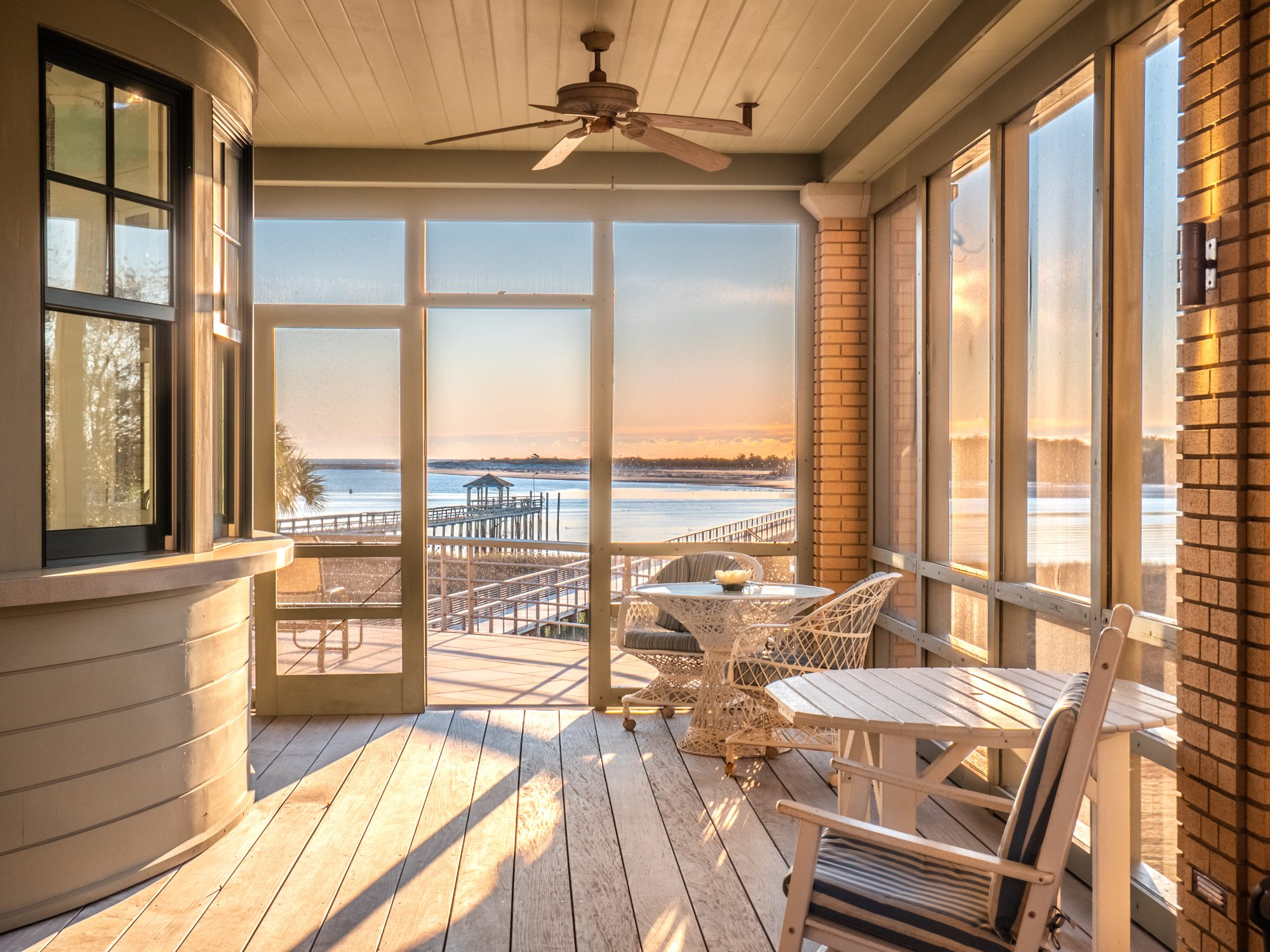 screened front porch with a water view. Wood decking. Brick pillars.
