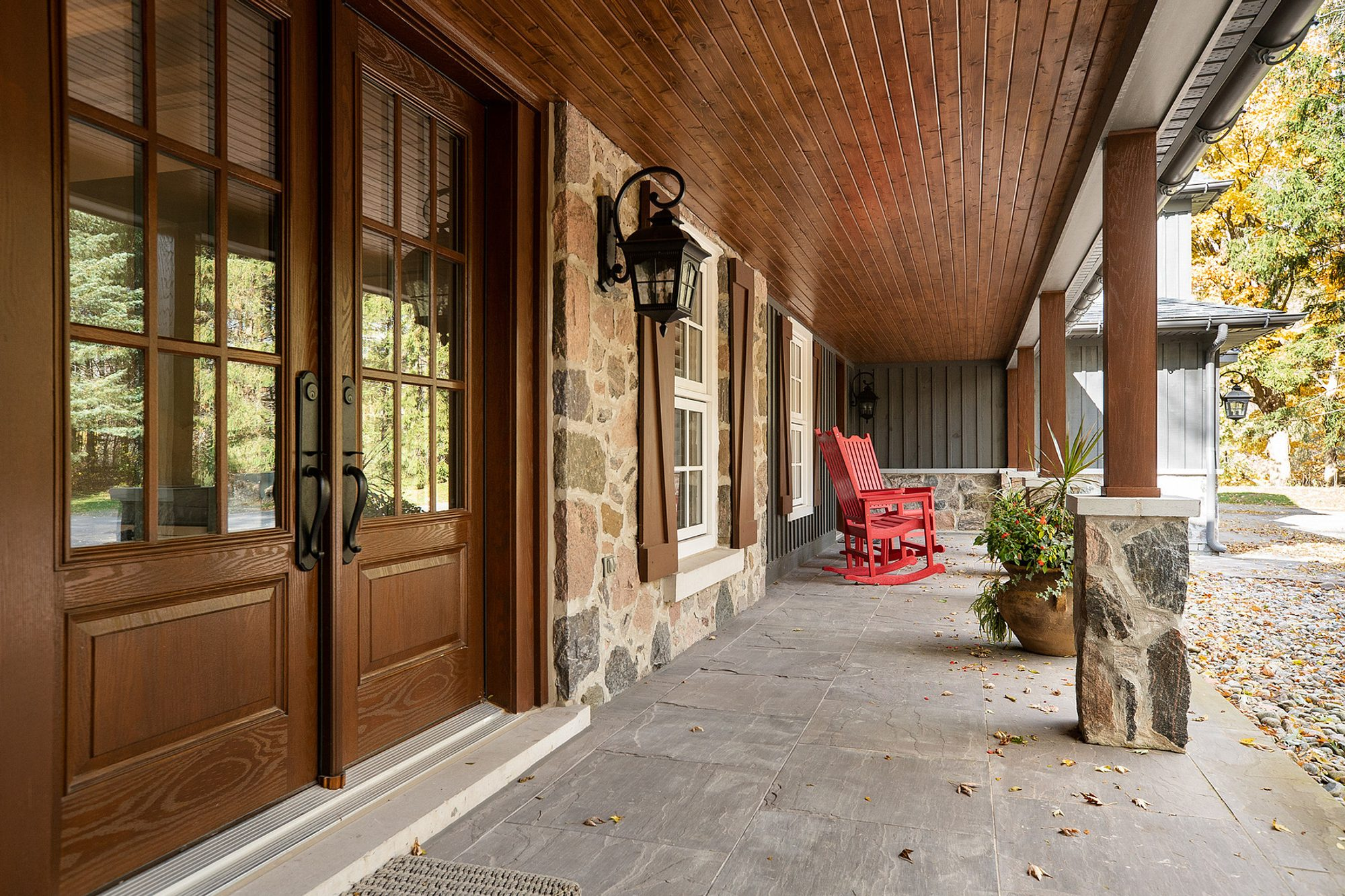 front porch with wood ceiling, stone siding veneer, french style front doors