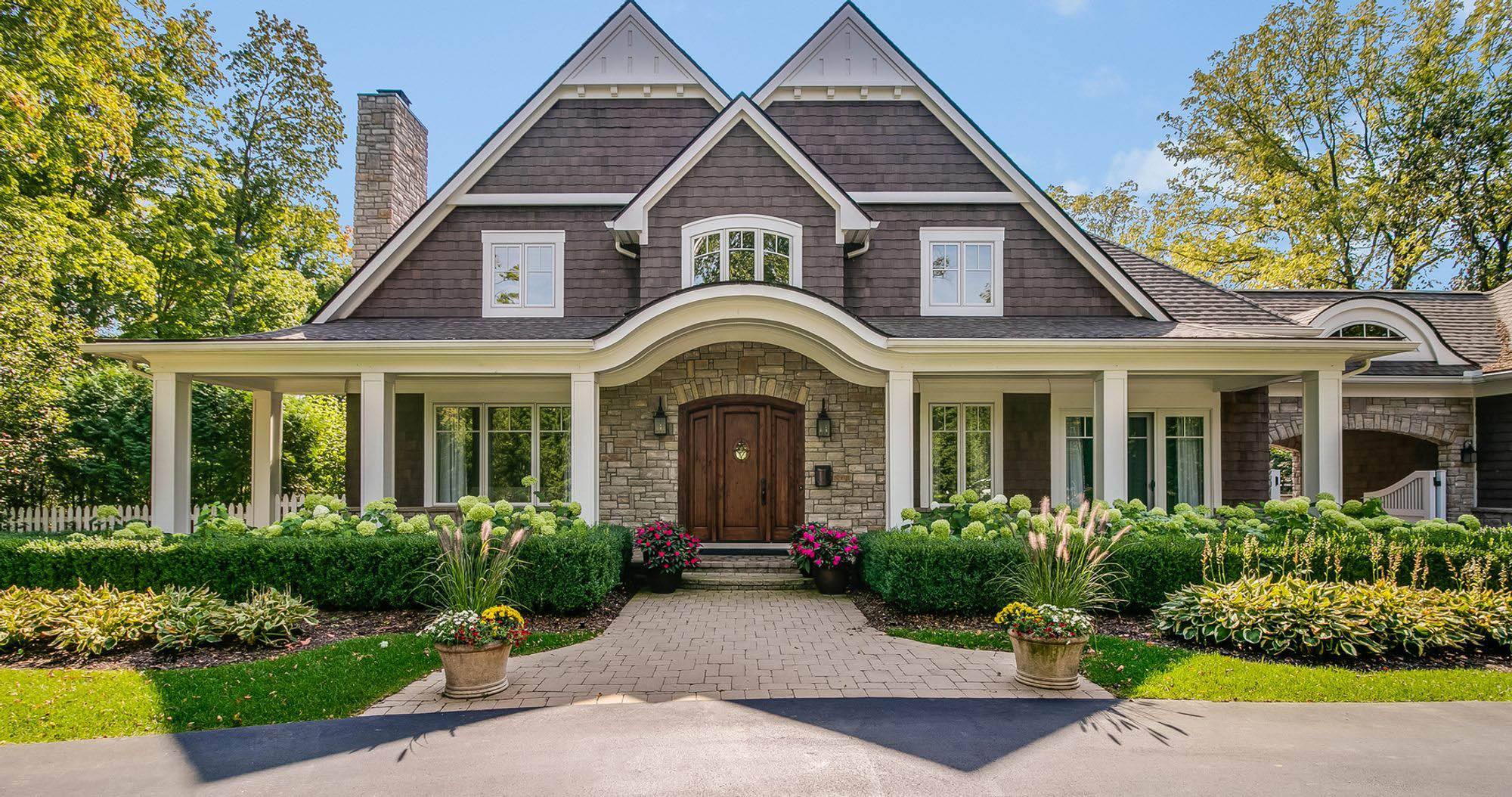 covered front porch with arch above the front door, real stone veneer, arched front door, cedar shake, front porch ideas