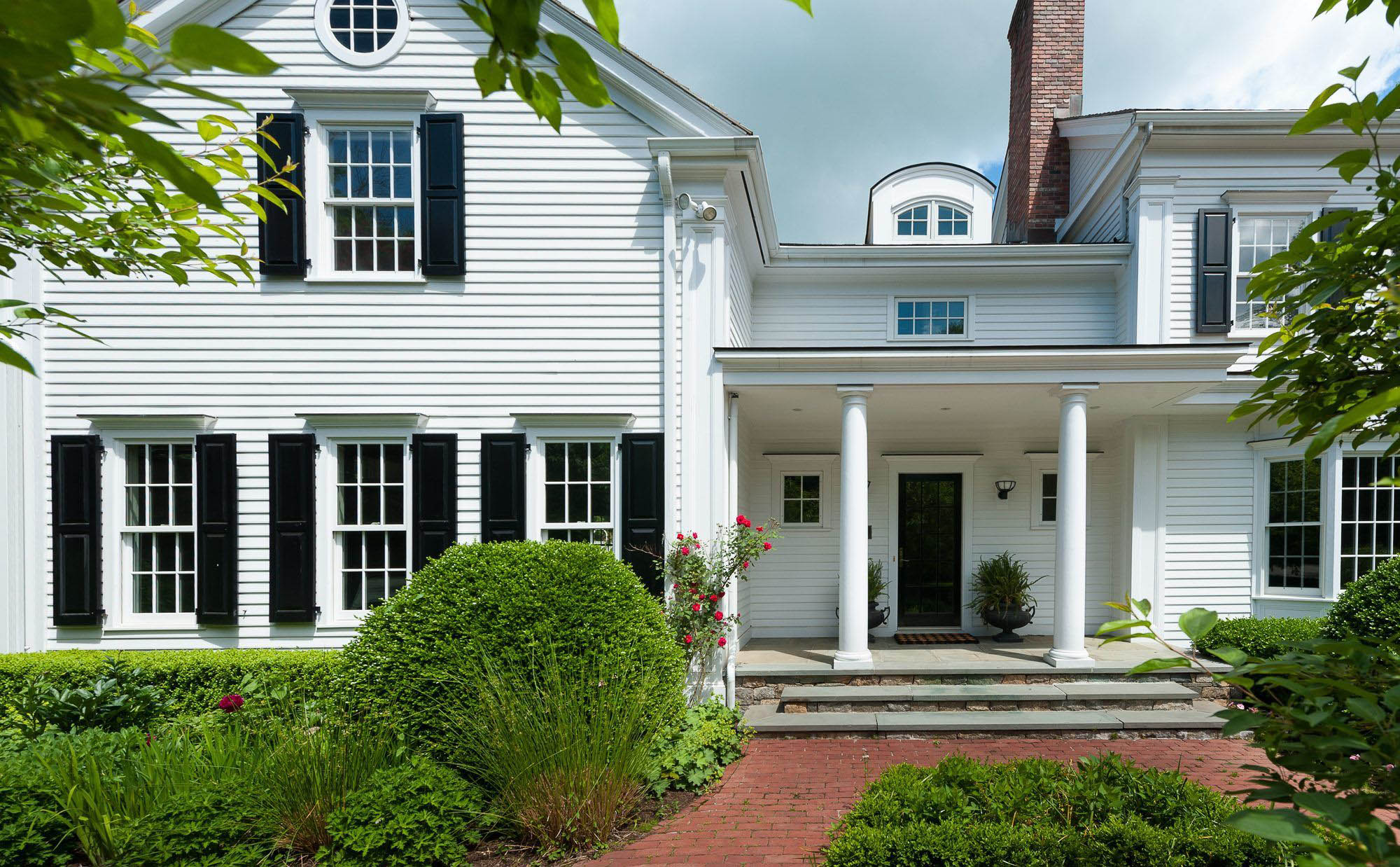 white Colonial style home with black shutters, white columns, blue stone, front covered porch. Front porch ideas.