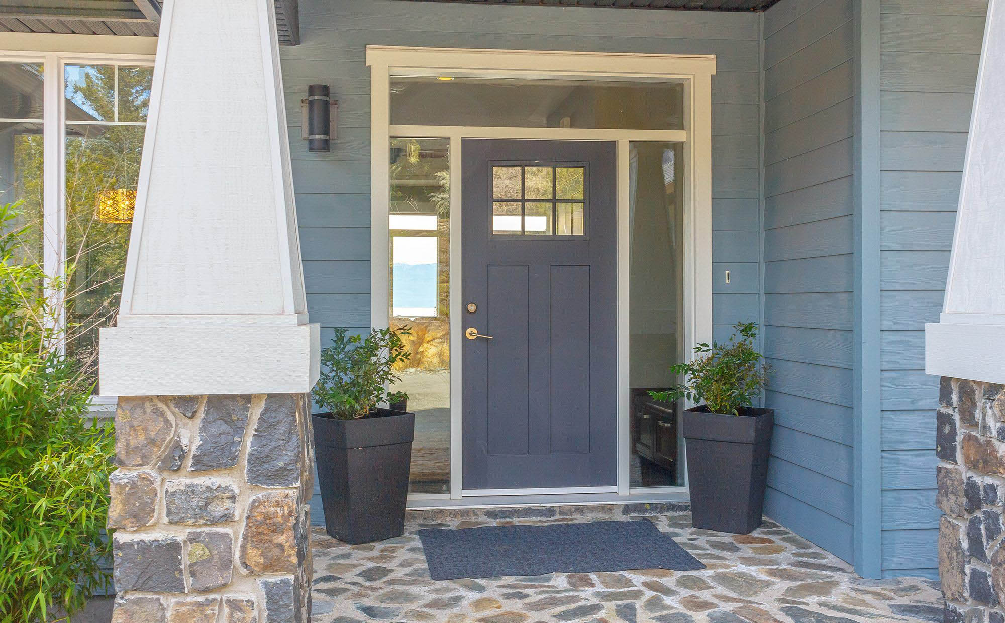 front porch design ideas, blue color scheme, blue siding and front door with dark blue planters, stone columns