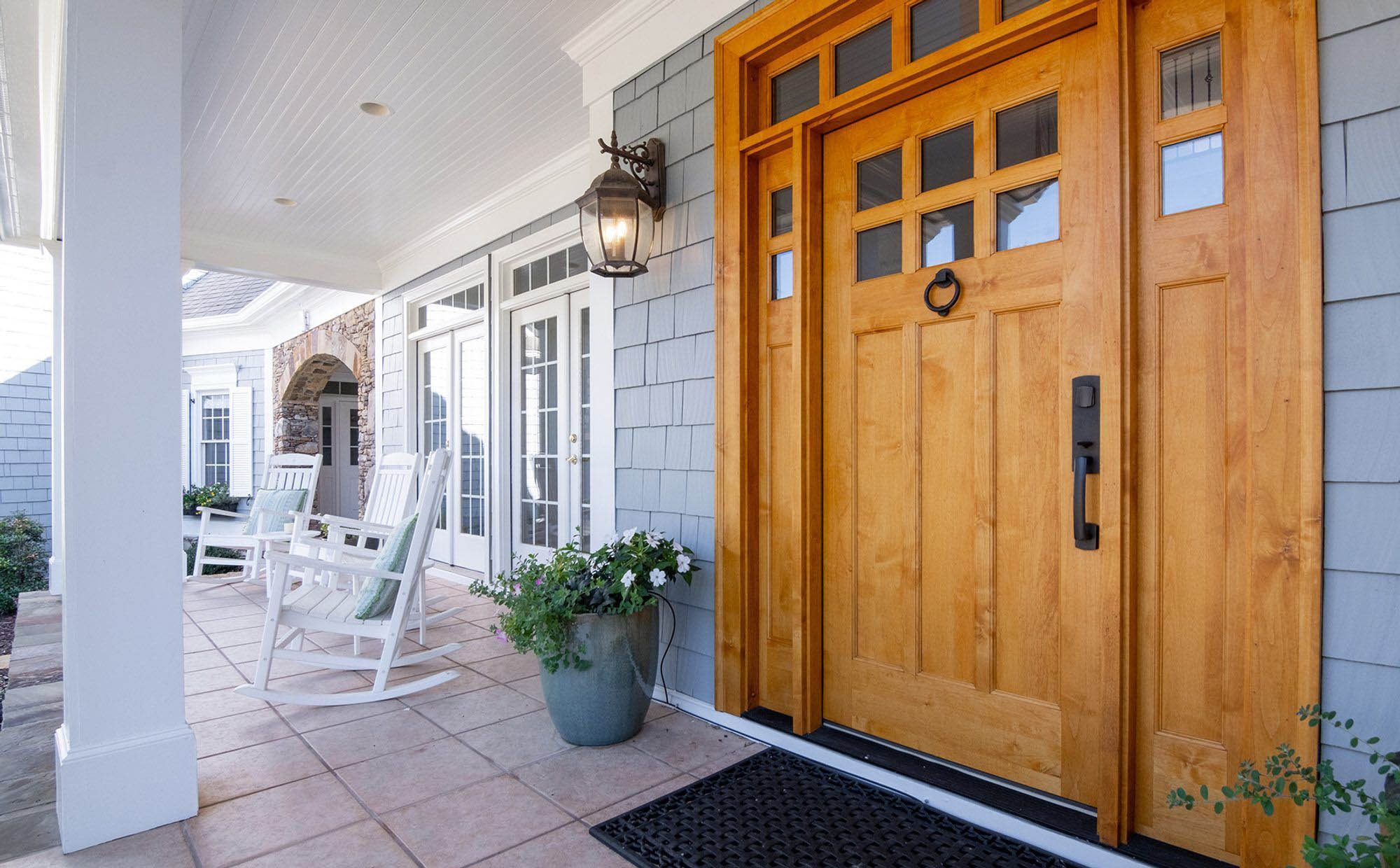 Front porch design wood front door with sidelights and transom, white beadboard soffit, tile floor.