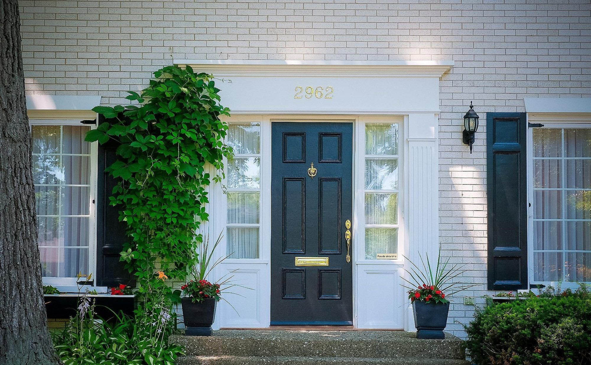 small open front porch with black front door and matching flower pots thick front door surround