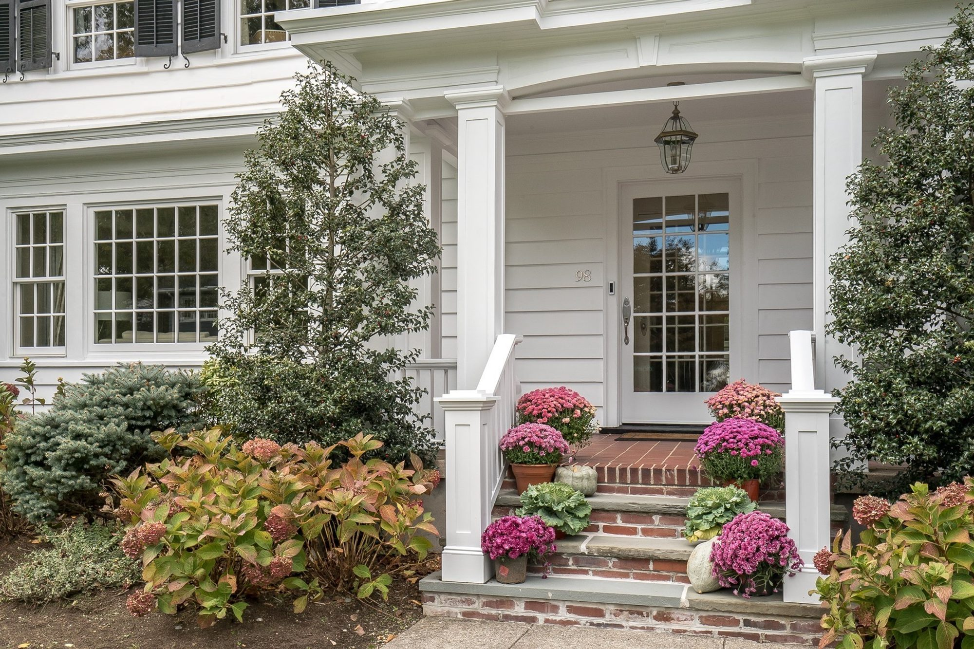 small red brick front covered porch with white columns and railings, stair flowers, simple pots, landscaping, white house black shutters