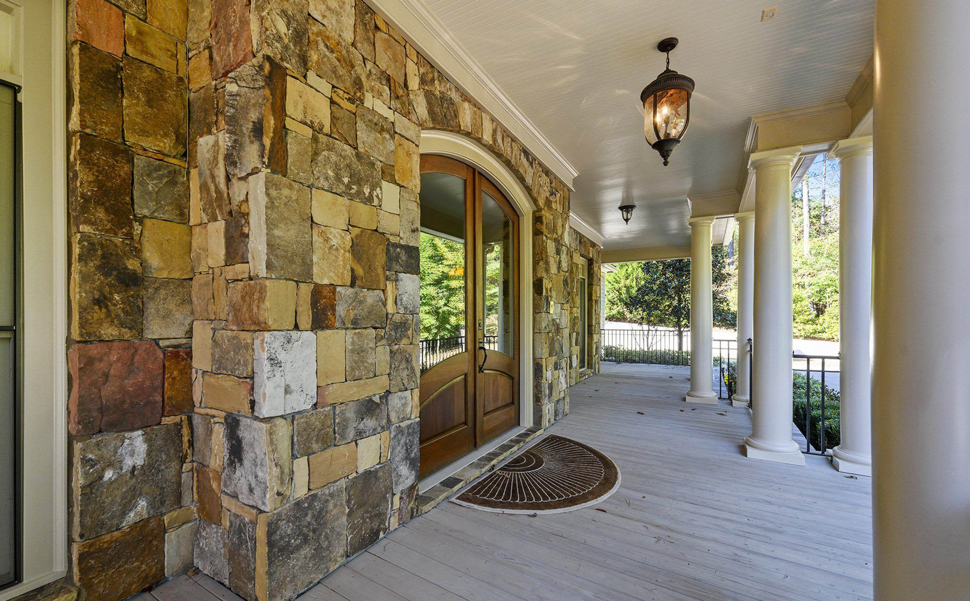 beautiful front porch design, earthy, natural color schene, brown & tan stone siding, wood front door, wood decking, columns. front porch design.