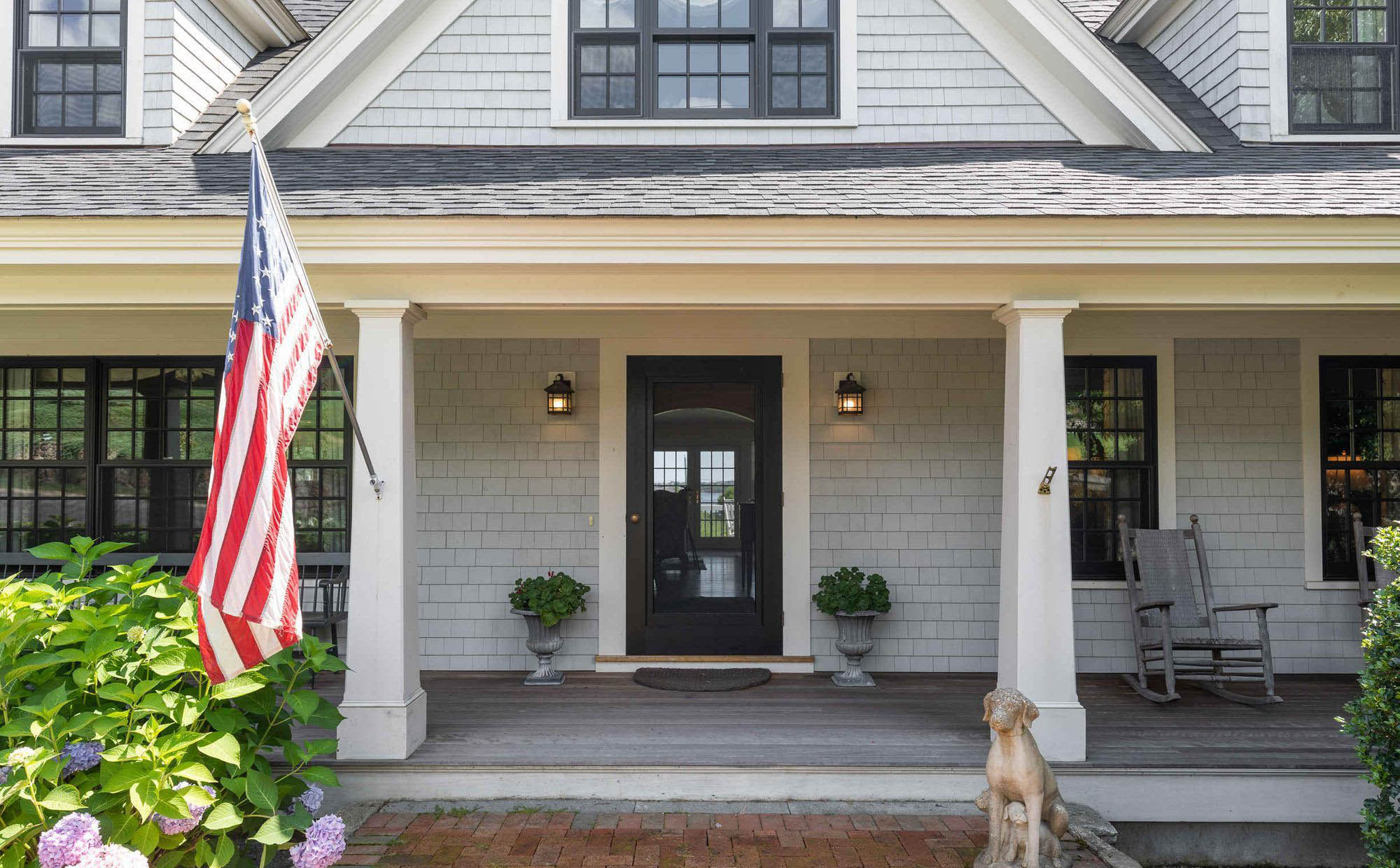 laid back comfortable front porch design, gray decking with weathered gray chairs, black front door