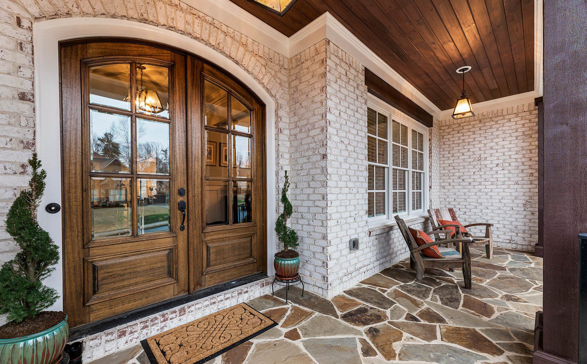 covered front porch ideas wood arched doors white washed brick stone floor porch plants wood chairs