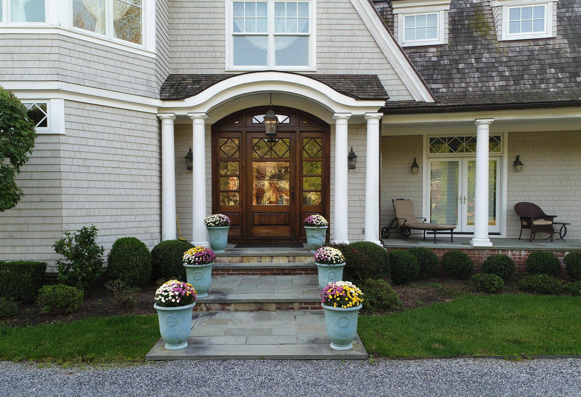 beautiful custom home covered front porch with arch, flower pots with porch flowers, bluestone and red brick