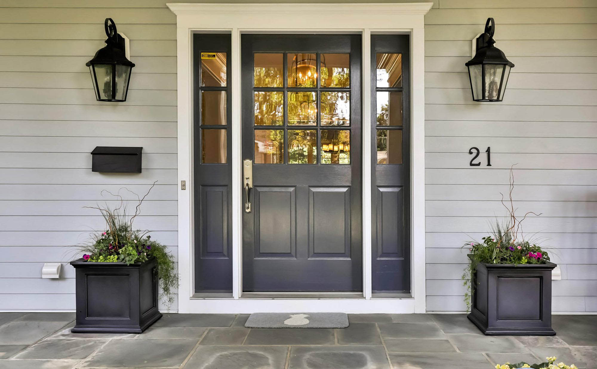 Black front door with matching flower planters, blue stone patio, sidelights, white trim.