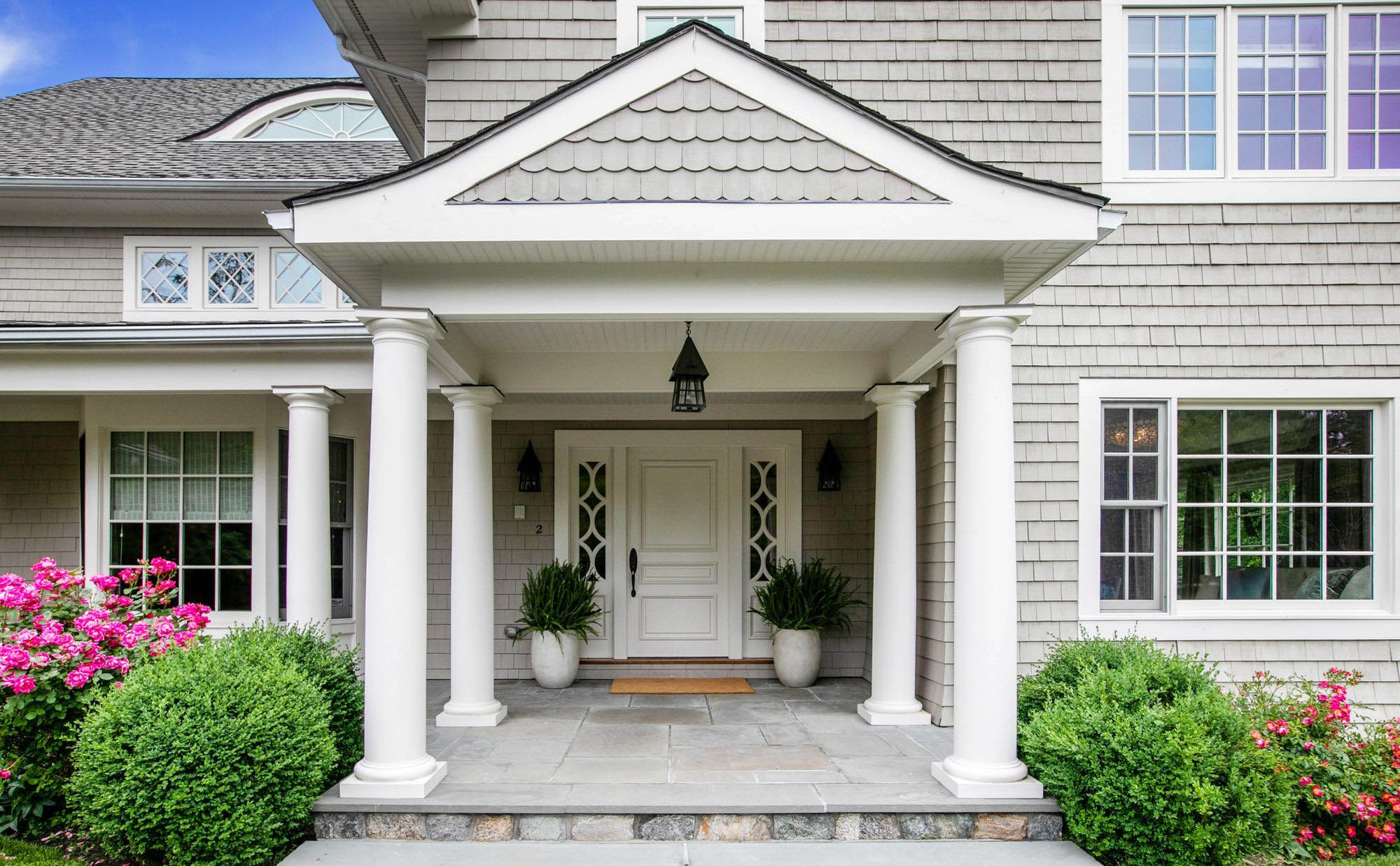 white front door with white side by side planters, white columns and trim, bluestone porch top, landscaping