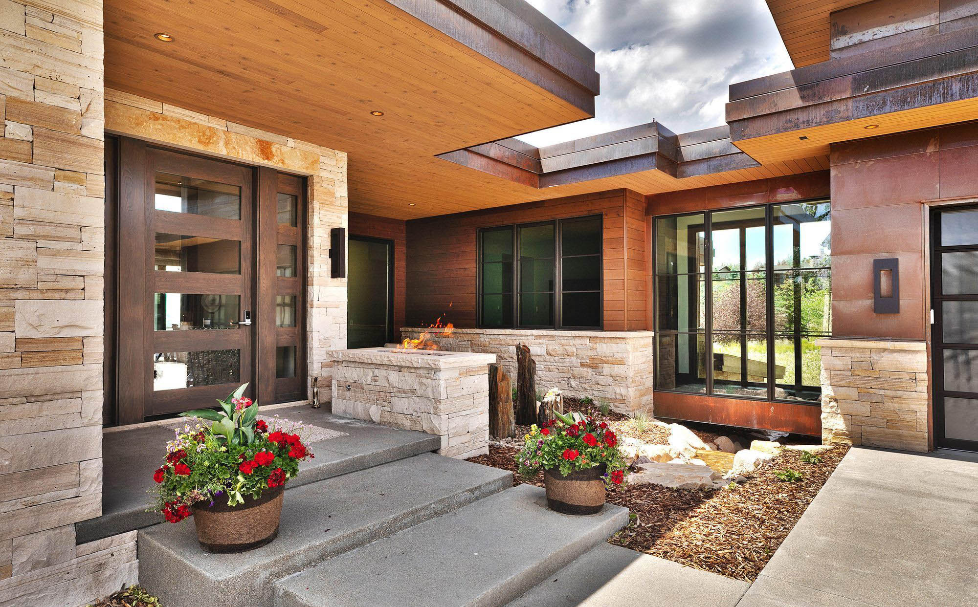 modern front porch design with cantilever roof, concrete porch, flowers and planters, real cream colored stone siding