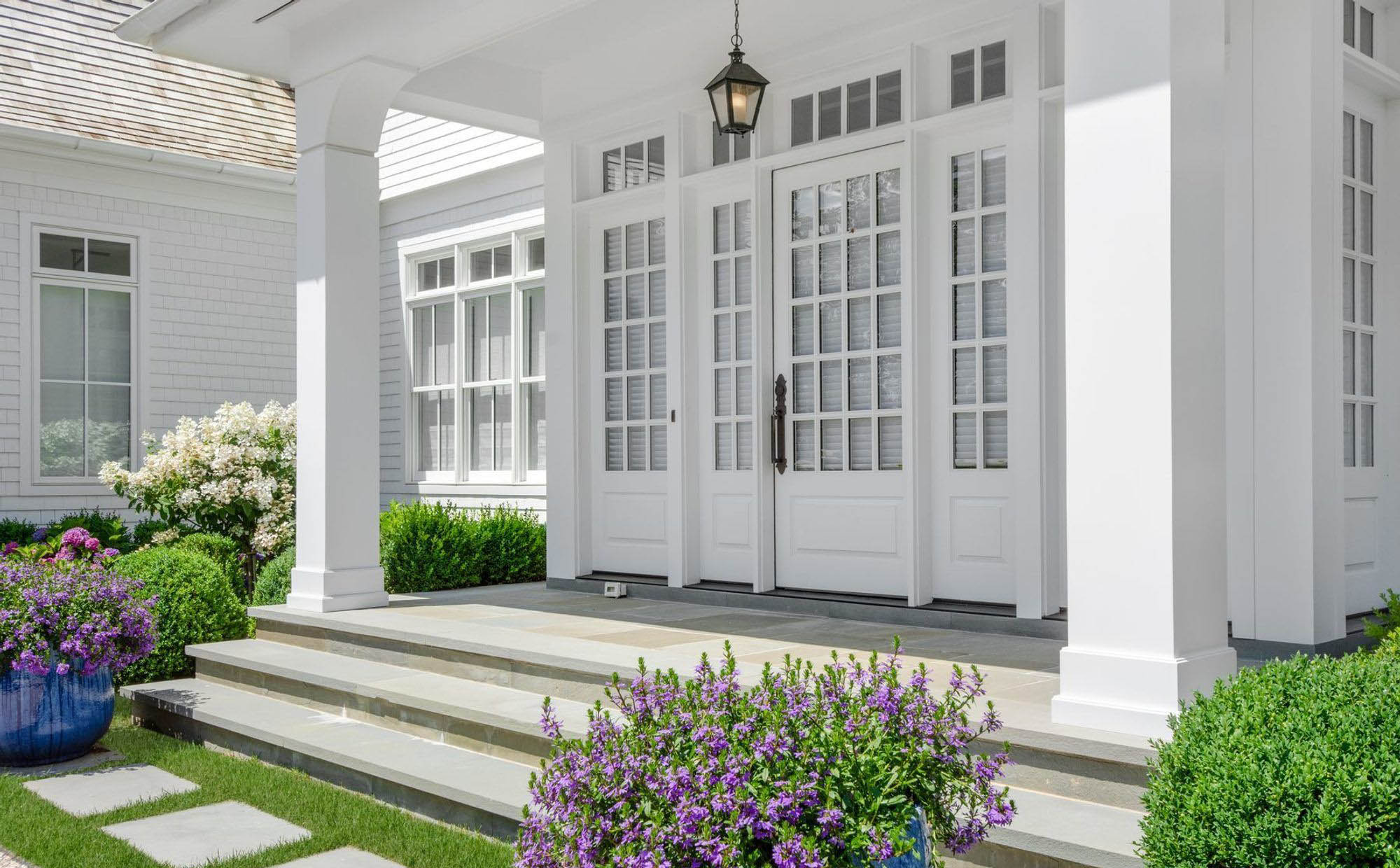 all white front porch with white siding, door, columns, trim and ceiling. black hardware and light fixture. bluestone porch top. potted flowers.